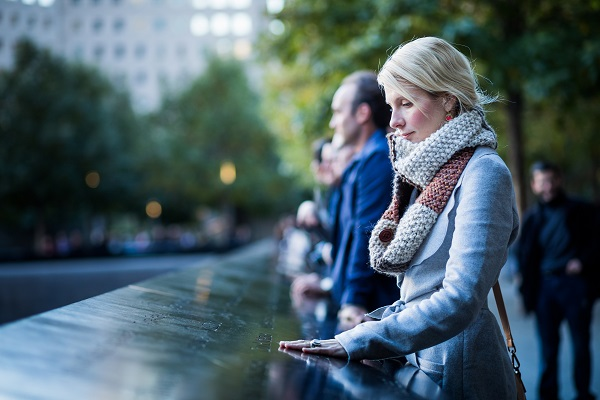 Woman taking a moment to reflect while viewing names at the September 11th memorial in New York City
