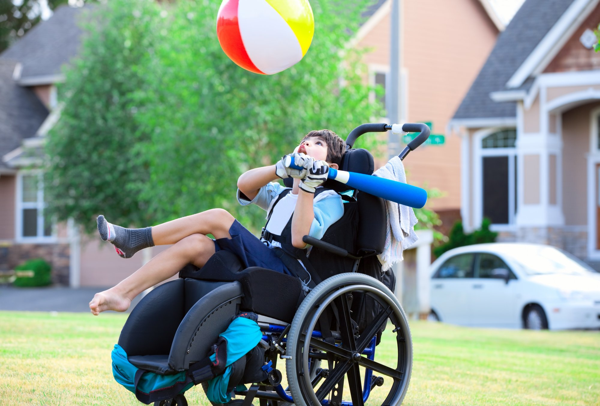 Boy with cerebral palsy plays with beachball in his wheelchair | Eisbrouch Marsh