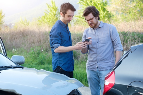 Men exchange information after a car accident