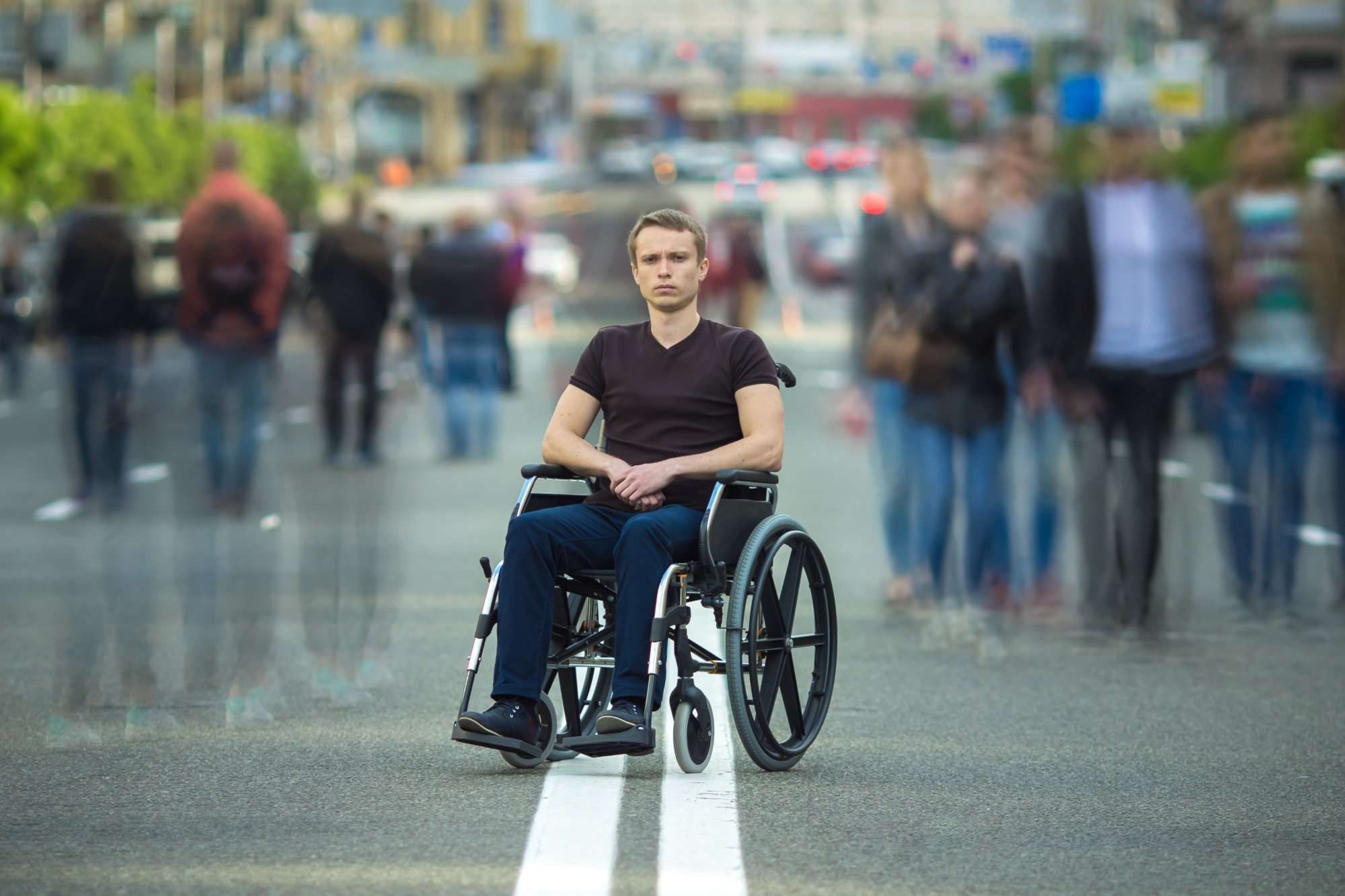 Young man in wheelchair sits in middle of road, opposite direction from crowd