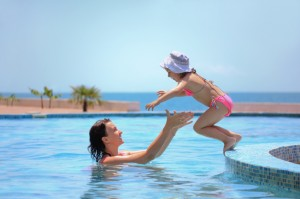 woman catches little girl jumping in pool against sea
